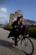 Cyclist passing in front of the A-Bomb Dome at Hiroshima's Peace Memorial Park.