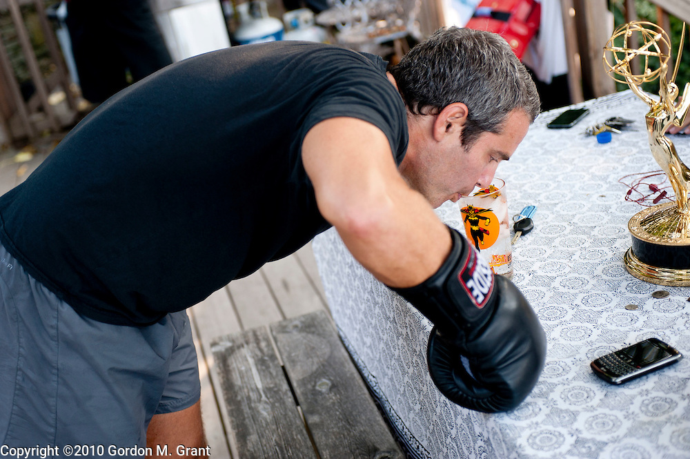 Sag Harbor, NY - 9/2/10 -   Andy Cohen of Bravo TV takes a drink of water during a boxing workout with Will Torres of Willspace Training on the deck of Cohen's home in Sag Harbor, NY September 2, 2010. The Emmy that Bravo TV won at the recent Emmy Awards is next to him. CREDIT: Gordon M. Grant for The Wall Street Journal<br /> HEARD_Bravo