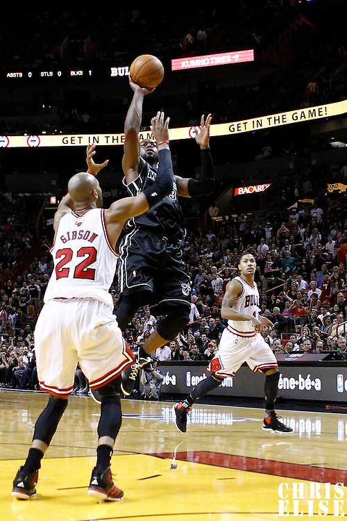 29 January 2012: Miami Heat shooting guard Dwyane Wade (3) takes a jumpshot over Chicago Bulls forward Taj Gibson (22) during the Miami Heat 97-93 victory over the Chicago Bulls at the AmericanAirlines Arena, Miami, Florida, USA.