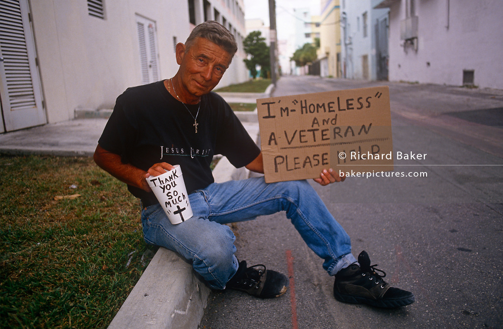A Christian homeless man and veteran holds a sign and a coffee cup asks for donations on 15th May 1996, in Miami Beach, Florida, USA.