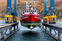 Commercial fishing vessel in the slings while being lowered back into the water in Kodiak, Alaska shipyard