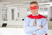 Portrait of serious businessman in superhero costume in office