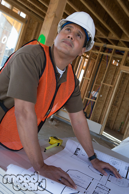 Construction worker examining blueprints inside half constructed house