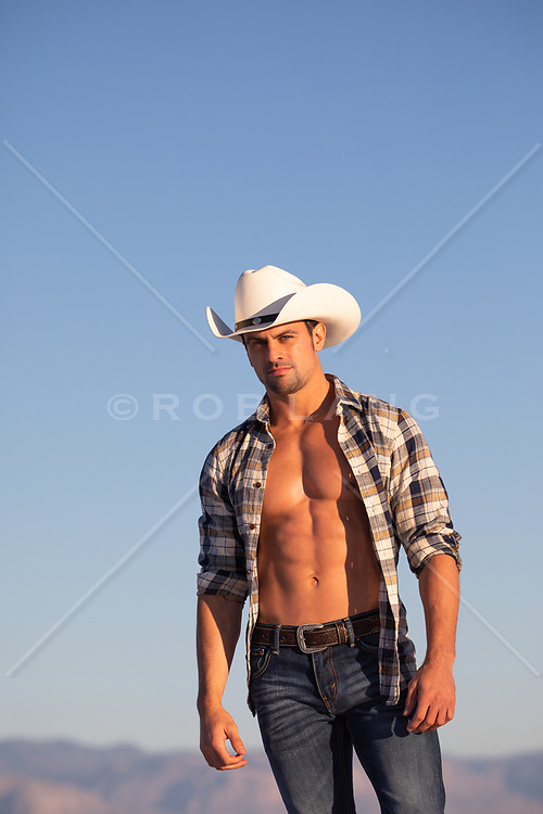 All American cowboy with open shirt outdoors on a ranch