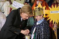 04 JUN 2008, BERLIN/GERMANY:<br /> Angela Merkel, CDU, Bundeskanzlerin, steckt ihre Spende in die Spendendose von einem der Heiligen drei Koenige, waehrend dem Empfang der Sternsinger im Bundeskanzleramt<br /> IMAGE: 20080104-01-024<br /> KEYWORDS: Heilige drei Koenige, Heilige drei K&ouml;nige, spendet, Geld, Geldscheine, Kanzleramt