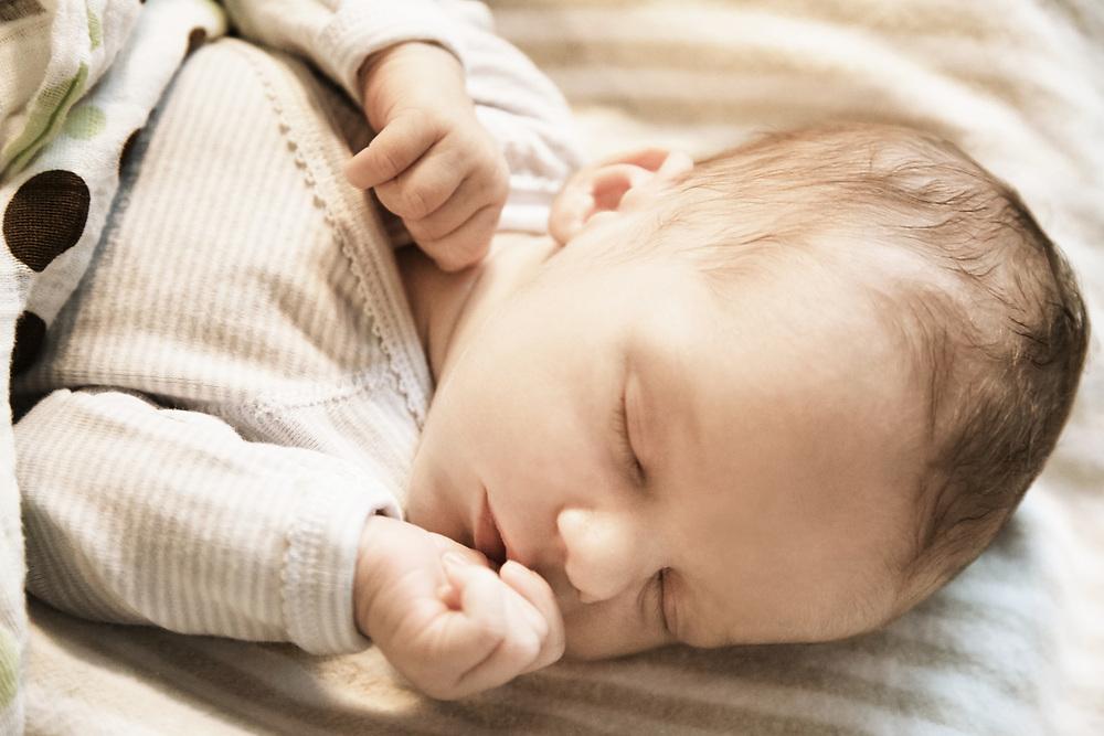 Baby asleep in crib sucking thumb