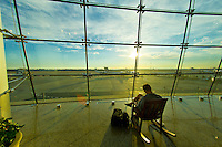 People waiting near a huge glass window at Sea-Tac International Airport, Seattle, Washington