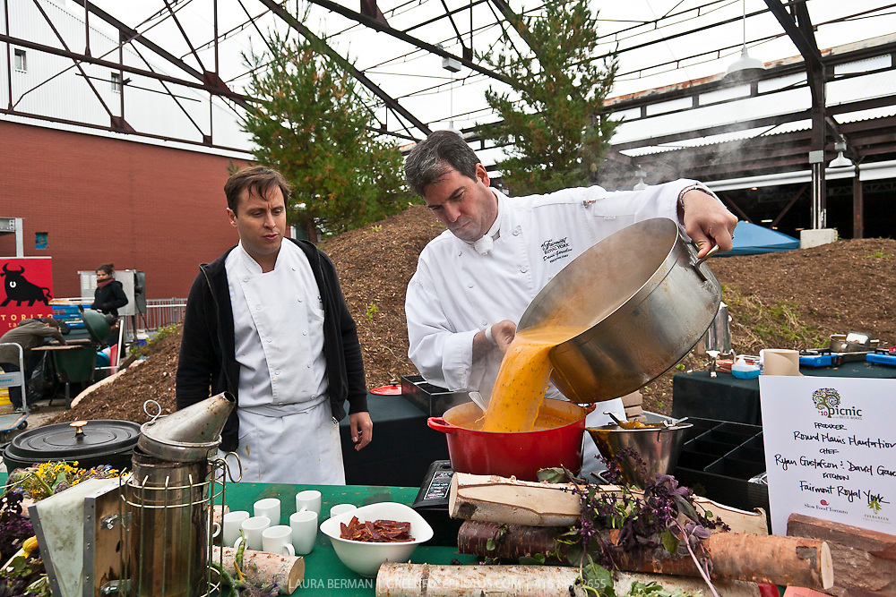 Royal York Hotel's Executive Chef David Garcelon pours a large quantitiy of  rich golden sauce as chef Ryan Gustaffson looks on at Slow Food's Picnic at the Brick Works in Toronto, 2010.
