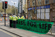 Met police officers talk at a banner on the north end of Waterloo Bridge on day 4 of protests by climate change environmental activists with pressure group Extinction Rebellion, on18th April 2019, in London, England. The Met have been criticised for allowing the protests to continue their occupations of major roads and junctions such as Waterloo Bridge and Oxford Circus.