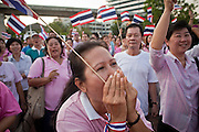 "Apr. 2, 2010 - BANGKOK, THAILAND: A pink shirt protestor covers her mouth while screaming obscenities directed to Red Shirt protestors who are disrupting life in Bangkok. Thousands of ""Pink Shirts,"" who claim to be neither ""Red Shirts"" nor ""Yellow Shirts"" nicknames for Thailand's dueling political forces, gathered in Lumpini Park in central Bangkok Friday evening to call for ""peace in the land,"" a play on the Red Shirts slogan, ""Red in the Land."" The ""Pink Shirts"" represented educators, business people and people in the tourist industry, all of which have been hurt by the ongoing political protests that have disrupted life in the Thai capital. The ""Pink Shirts"" stressed their loyalty to His Majesty Bhumibol Adulyadej, the King of Thailand, and chanted for the Red Shirts to ""Get Out!"" of Bangkok.    PHOTO BY JACK KURTZ"