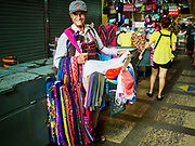 10 JULY 2018 - NAKHON PATHOM, THAILAND:  A man sells aprons and cloth bags in the market in Nakhon Pathom. Nakhon Pathom is about 35 miles west of Bangkok. It is one of the oldest cities in Thailand, archeological evidence suggests there was a settlement on the site of present Nakhon Pathom in the 6th century CE, centuries before the Siamese empires existed. The city is widely considered the first Buddhist community in Thailand and the nearly 400 foot tall Phra Pathom Chedi is considered the first Buddhist temple in Thailand.    PHOTO BY JACK KURTZ
