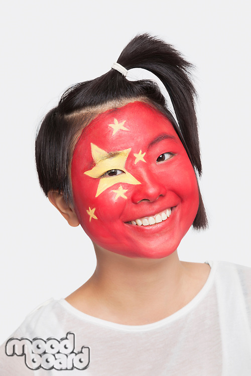 Portrait of young Asian woman with Chinese flag painted on face against white background