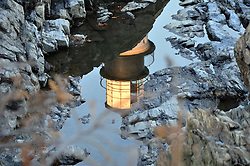 Reflection of Portland Head Lighthouse in still water.