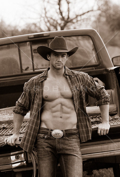 sexy cowboy with an open shirt leaning against a truck