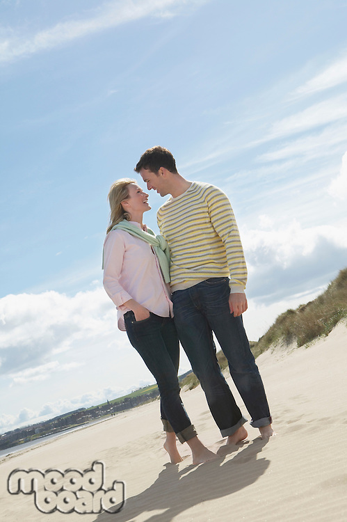 Couple standing face to face on beach