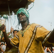 Carnival dancer in Brazil wearing a gold outfit and embridered green hat