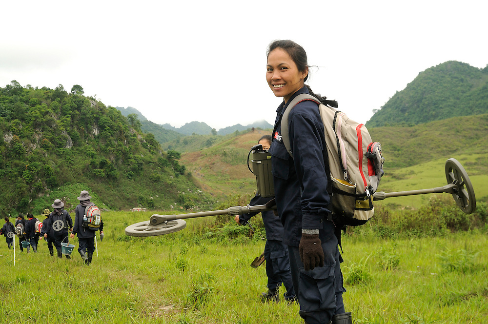 "Mines Advisory Group, Technician, Vonekham Dalavong, age 29, uses a metal detector to uncover live bombs hidden in the soil.  She and her partner, Sia, said, ""The first time we found a bomb we were afraid.  But we have good training and team work.  We have found many bombs, now it is just normal.  But, if we see a snake - we drop everything and run!"" ..Laos was part of a ""Secret War"", waged within its borders primarily by the USA and North Vietnam.  Many left over weapons supplied by China and Russia continue to kill.  However, between 90 and 270 million fist size cluster bombs were dropped on Laos by the USA, with a failure rate up to 30%.  Millions of live cluster bombs still contaminate large areas of Laos causing death and injury.  The US Military dropped approximately 2 million tons of bombs on Laos making it, per capita, the most heavily bombed country in the world.. .The women of Mines Advisory Group (MAG) work everyday under dangerous conditions removing unexploded ordinance (UXO) from fields and villages...***All photographs of MAG's work must include (either on the photo or right next to it) the credit as follows:  Mine clearance by MAG (Reg. charity)***."