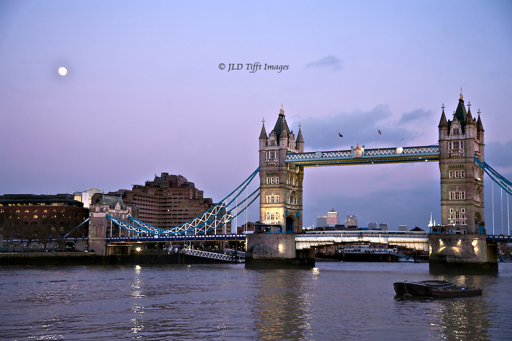 View of Tower Bridge, London, at dusk.  The sky and river water are pink and purple, and lights on the bridge are lit.