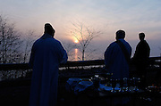 SUNRISE OVER LAKE MICHIGAN -- Fr. Ron Gramza, left, pastor of Divine Mercy Parish in South Milwaukee, joins parishioners as they watch the sun rise over Lake Michigan. Over 400 people turned out for the sunrise Easter Mass at Grant Park, located on a bluff overlooking Lake Michigan. (Catholic Herald photo by Sam Lucero)