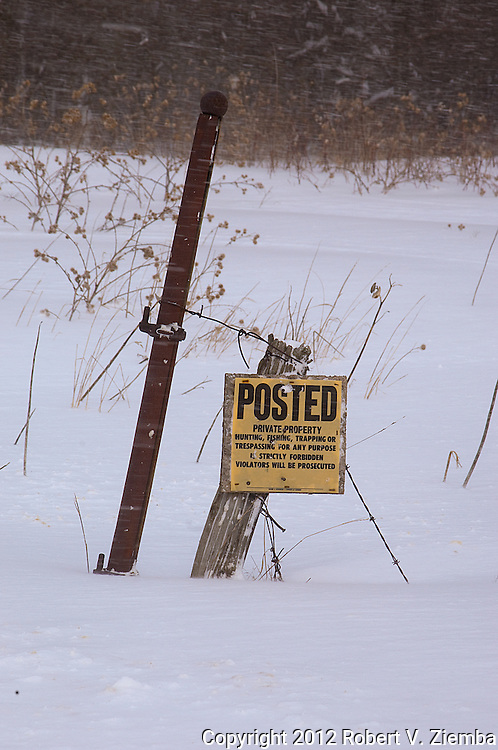 """Posted""-An image of a posted, no trespassing sign on an old fence post in the snow."