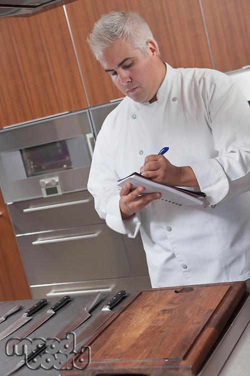 Mid- adult chef stock-taking in notebook