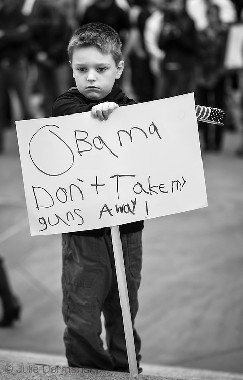 """January 18, Baton Rouge , 7 year old Caden at a pro-gun rally organized by """"Guns across America"""" on """"Gun Appreciation Day"""", holds a sign with a message for President Obama. His mother read a letter he wrote to the president asking for him to let his teacher and mother have guns during the rally. After the massacre at  a school in Sandy Hook, Connecticut , the debate over gun control in America became a key political issue."""
