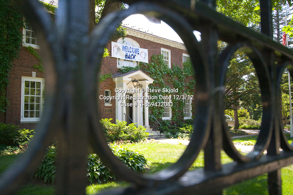 Entrance to historic Macalester College Alumni House viewed thru wrought iron fence. St Paul Minnesota MN USA