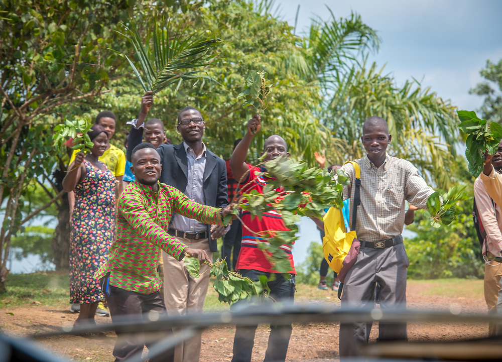 A group of people wave palms in greeting in Ganta,Liberia