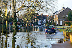 © Licensed to London News Pictures. 12/01/2014. Wraysbury, UK. A car makes its way through the water. Flooding in Wraysbury, Berkshire today 12th January 2014.  Flooding and property damage is expected to continue along the River Thames.  Large areas of Britain are experiencing flooding after wet weather. Photo credit : Stephen Simpson/LNP