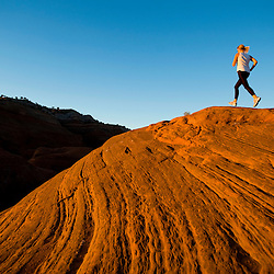A woman runs on slick rock near Gallup, New Mexico.