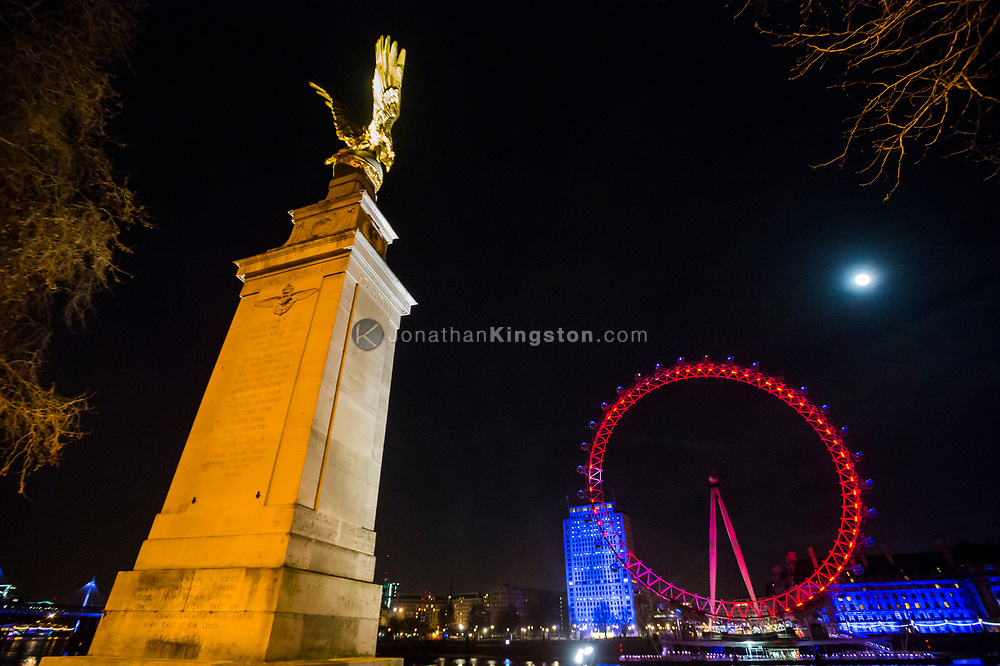 Night view of the Royal Air Force Memorial with the London Eye, illuminated in red with County Hall illuminated in blue, in the background in London, England.