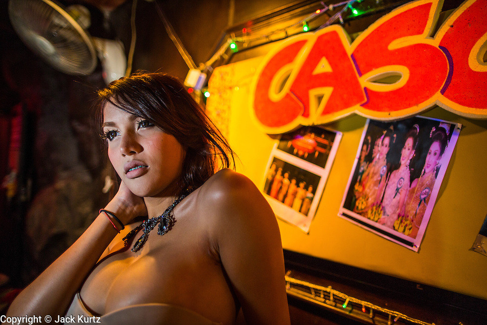 "18 JANUARY 2013 - BANGKOK, THAILAND: A transgendered sex worker waits for customers in the Nana Entertainment District in Bangkok. Prostitution in Thailand is technically illegal, although in practice it is tolerated and partly regulated. Prostitution is practiced openly throughout the country. The number of prostitutes is difficult to determine, estimates vary widely. Since the Vietnam War, Thailand has gained international notoriety among travelers from many countries as a sex tourism destination. One estimate published in 2003 placed the trade at US$ 4.3 billion per year or about three percent of the Thai economy. It has been suggested that at least 10% of tourist dollars may be spent on the sex trade. According to a 2001 report by the World Health Organisation: ""There are between 150,000 and 200,000 sex workers (in Thailand).""          PHOTO BY JACK KURTZ"