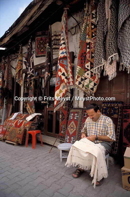 SAFRANBOLU, TURKEY AUGUST 2003. A carpet dealer mends his carpets. The city of Safranbolu positioned in the forests on the Black Sea coast is one of the world heritage sites of the UNESCO. Apart from its Ottoman era wood and mudbrick houses it is also known for its 'Lokum' or Turkish delight. A delicate sweets with flavours from nuts to rose petals. Photo by Frits Meyst/Adventure4ever.com
