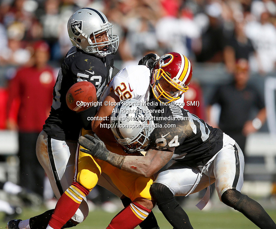 September 29, 2013 - Oakland, CA, USA - The Oakland Raiders' Charles Woodson (24) forces a fumble against Washington Redskins' Roy Helu, Jr. (29) in the fourth quarter at the O.co Coliseum in Oakland, California, Sunday, September 29, 2013. Due to a Raiders penalty, the play was negated. The Redskins defeated the Raiders, 24-14