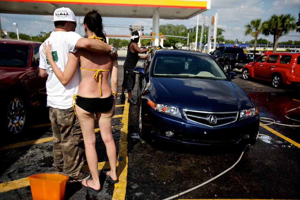 "Promoter Shannon Fuller, background, puts on a bikini car wash to help promote hip hop artist Theodore Wilson, left, a.k.a ""Hylo Griffix,"" album ""Full Clip"" at a gas station on U.S. 41 in San Carlos Park, Fla. Melissa Rogers, second from left, came to be a bikini girl, help wash cars and support her friend and his pursuit of his music."