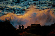 A couple watch the winter surf at the Devil's Punch Bowl on the Oregon, Coast.