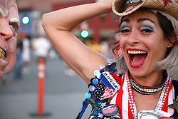 """A group of women outside the DNC dressed up as cartoonish patriotic girls """"from Crawford, Texas."""" One holds a paper mache puppet with the likeness of Bush on one side and McCain on the other."""