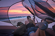A woman and her pet boxer dog enjoy the sunset while sitting inside a camp tent on the beach.