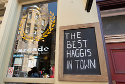 Sign outside Arcade haggis and whisky restaurant on Cockburn Street in Old Town of Edinburgh, Scotland ,UK