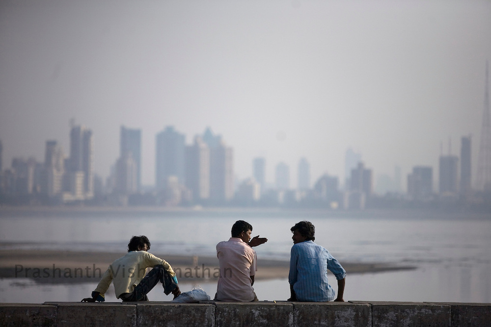 A group of Indian men relax at a waterfront in Mumbai, Tuesday, March 18, 2008. Western style dating is not common in India and young men are often left to spend time with each other or to flirt with women from a distance via SMS.(International Herald Tribune/Prashanth Vishwanathan)