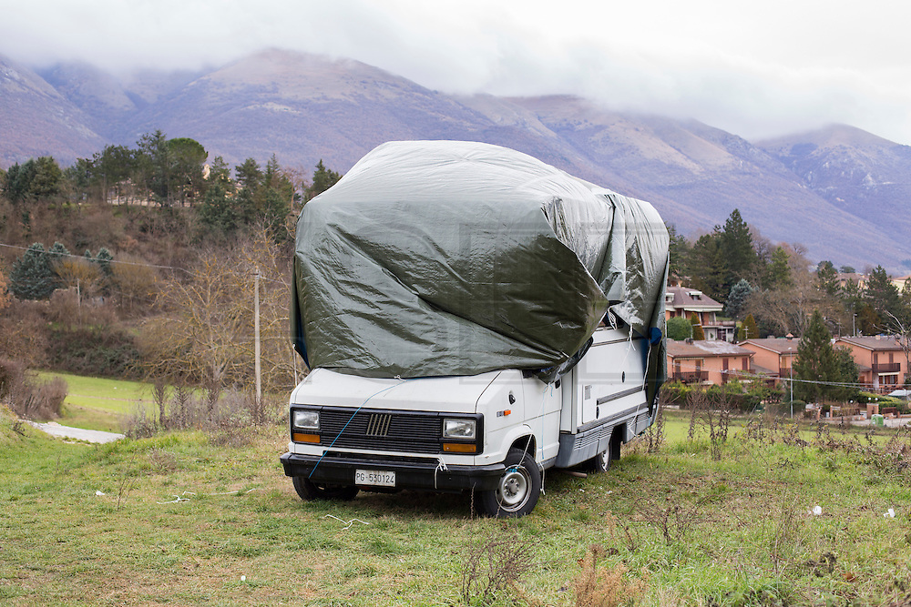 A caravan on a ground outside Norcia. There is a plastic sheet to help to protect from rain and cold.