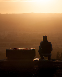 © Licensed to London News Pictures. 20/05/2015. Glastonbury, UK. A man watching the sunrise from Glastonbury Tor this morning, 20th May 2015. The day has started off clear, with early morning temperatures near freezing in places in the south west of England. Photo credit : Rob Arnold/LNP