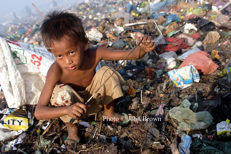 A young worker grasps the gaff he is using to collect soft clear plastic at The Stung Meanchey Landfill in Phnom Penh, Cambodia. Over 700 tons of garbage is dumped there daily.