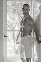 nude muscular man in a doorway at home