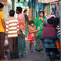 Jhumur Das and her daughter Shobnam Das (age 7) walk through one of the small network of lanes that run through Horijon Polli. Jhumur and her husband are both employed as cleaners. <br />