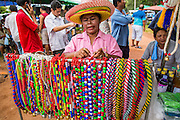 03 NOVEMBER 2012 - HAT YAI, SONGKHLA, THAILAND:   A woman sells decorative beads and lassos for bull owners at the bullfighting arena in Hat Yai, Songkhla, Thailand. The bulls wear the beads and lassos before their fights. Bullfighting is a popular past time in southern Thailand. Hat Yai is the center of Thailand's bullfighting culture. In Thai bullfights, two bulls are placed in an arena and they fight, usually by head butting each other until one runs away or time is called. Huge amounts of mony are wagered on Thai bullfights - sometimes as much as 2,000,000 Thai Baht ($65,000 US).     PHOTO BY JACK KURTZ