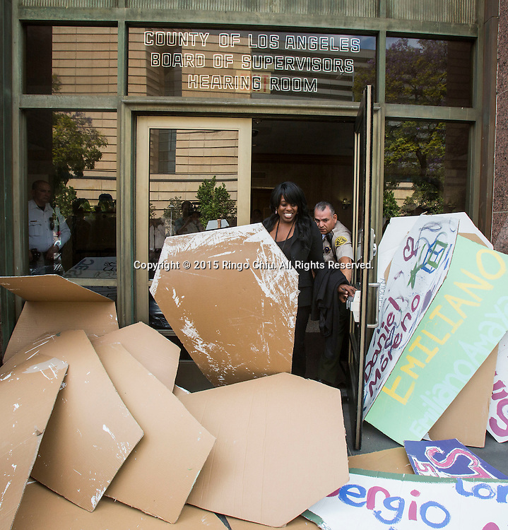 A woman tries to leave the Kenneth Hahn Hall of Administration as the entrance is blocked by the makeshift coffins on April 7, 205 during the 'Remember Me' march for people who have been killed by law enforcement. Over 617 people have been killed by LAPD since 2000, according to the organization youth4justice. (Photo by Ringo Chiu/PHOTOFORMULA.com)