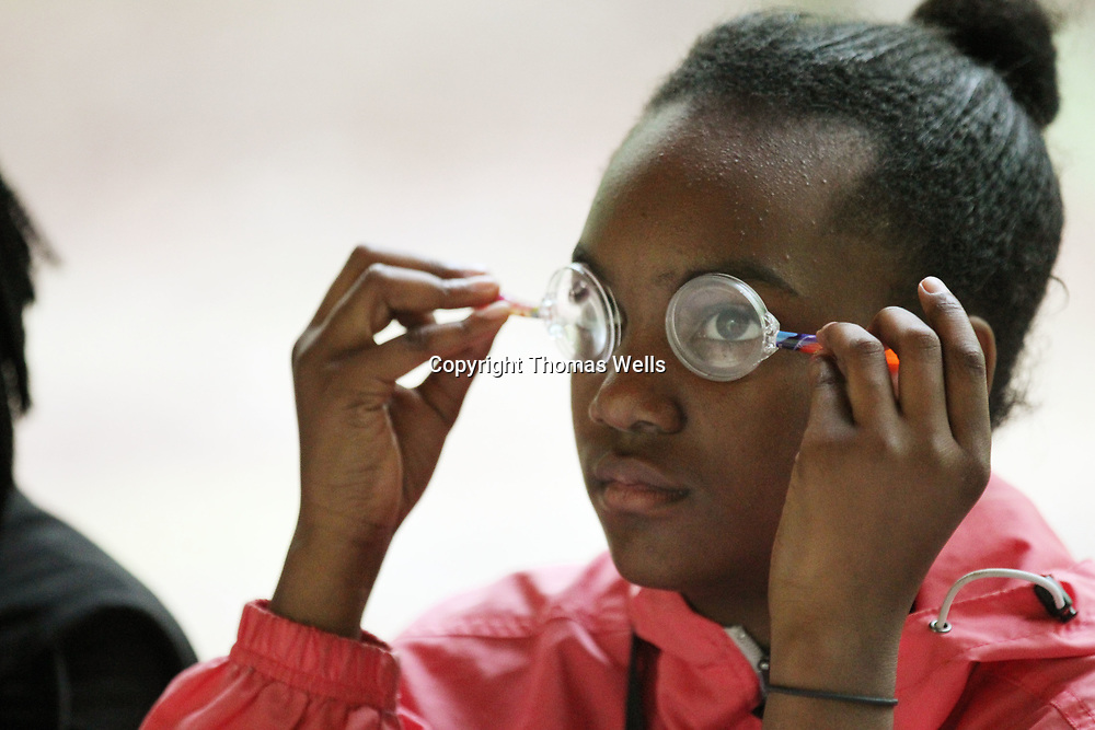 Kamryn Harris plays with her magnifying glass pens duirng Thursday's enviromental camp at the Natchez Trace Parkway.