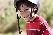 Young skateboarder smiles at the camera outside with natural green background - shallow depth of field