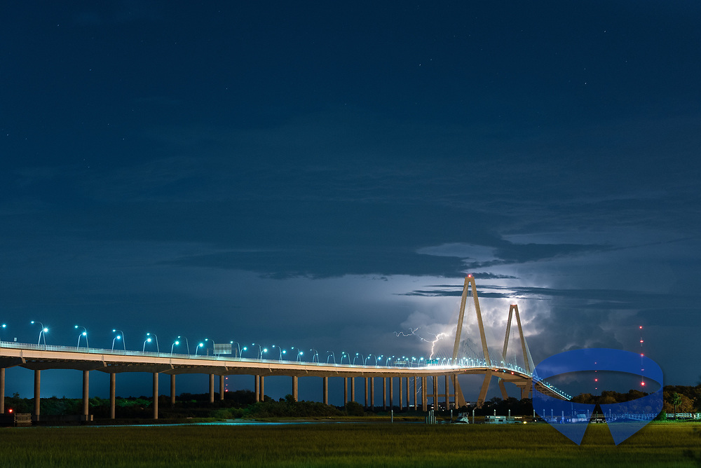 A late evening summer storm in Charleston, South Carolina, produces a show of lightning in the distance behind the Arthur Ravenel Jr. bridge.